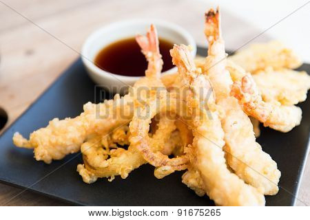 asian kitchen, food, culinary and cooking concept - close up of deep-fried tempura shrimps with soy sauce on table at restaurant