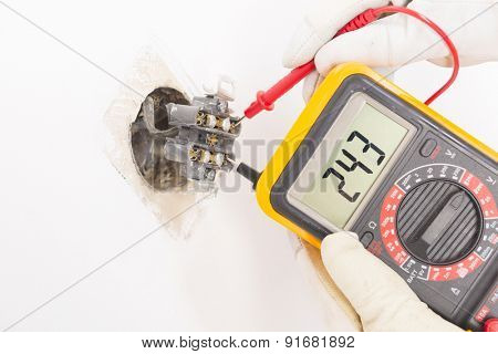 Electrician checking socket voltage with digital multimeter poster