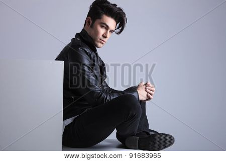 Side view picture of a fashion man sitting on the floor, looking at the camera while holding his hands together.