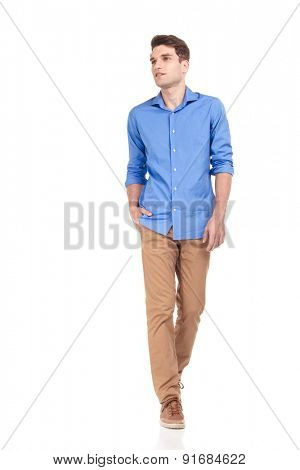 Handsome young casual man walking with his hand in pocket on isolated background, looking away from the camera.