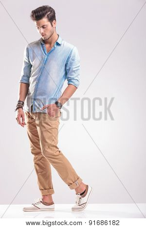 Full length picture of a young casual man walking with his hand in pocket while looking down.
