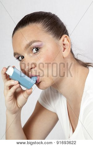 Pretty girl using an asthma inhaler for preventing attacks
