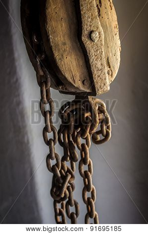 Old Sheave with hanging rusty chains