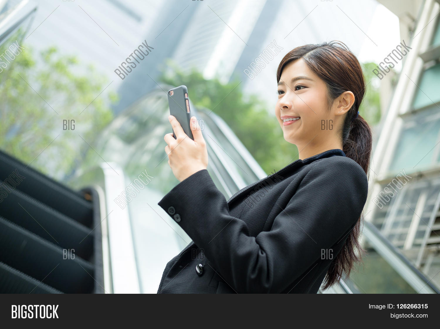 Business woman read on cellphone and standing on escalator