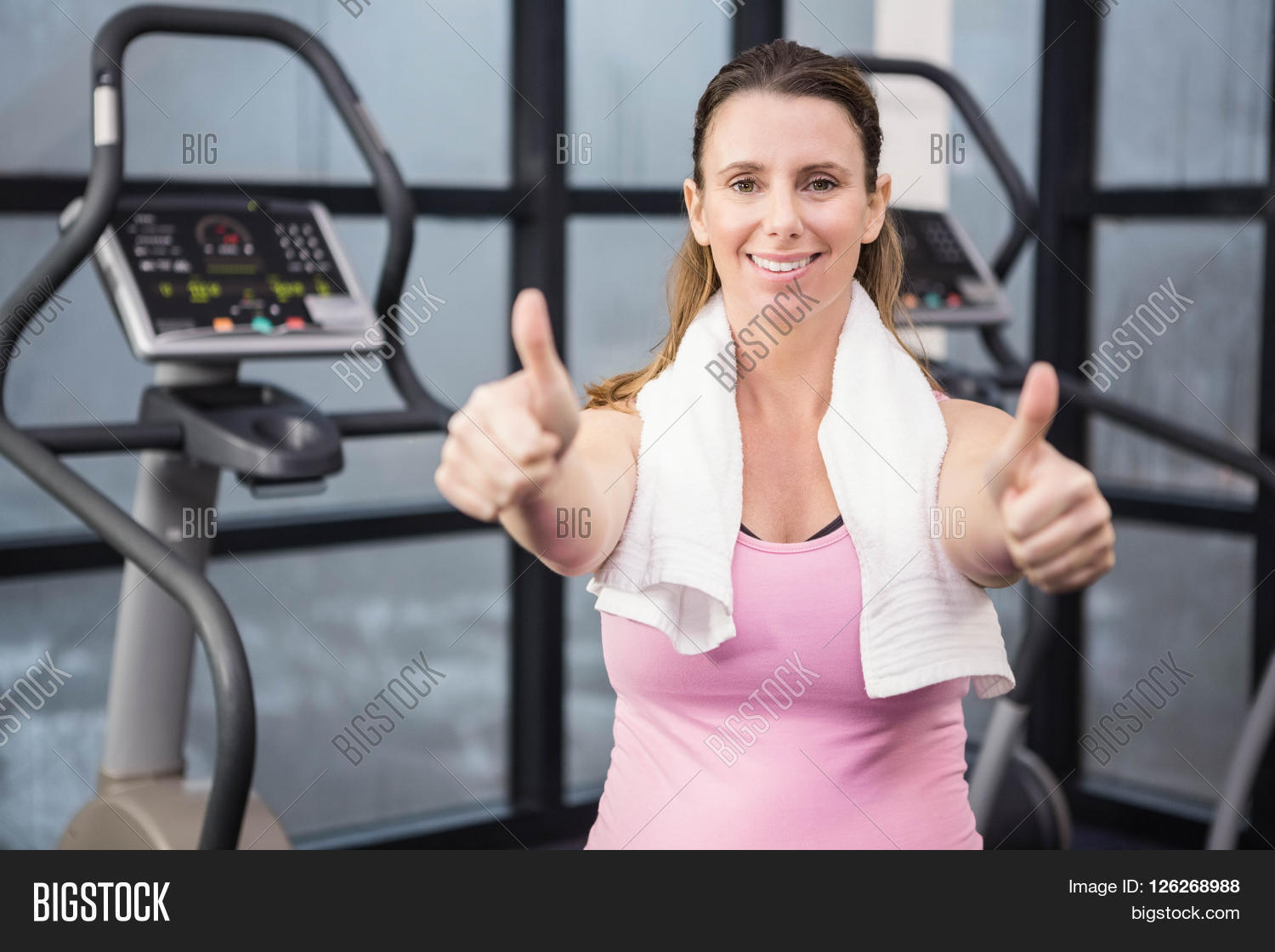 Happy pregnant woman showing thumbs up at the gym