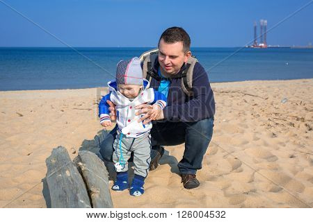 First steps of little baby boy with his father at the beach