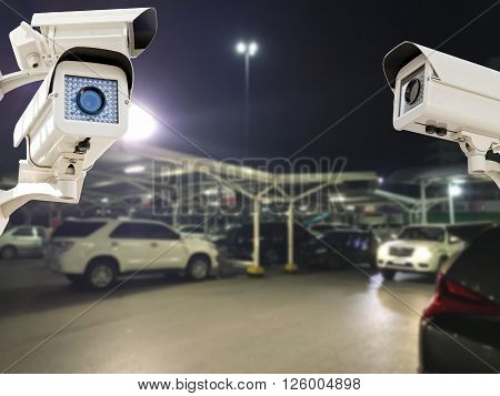 The CCTV Security Camera operating in parking lot car at night time blur background.