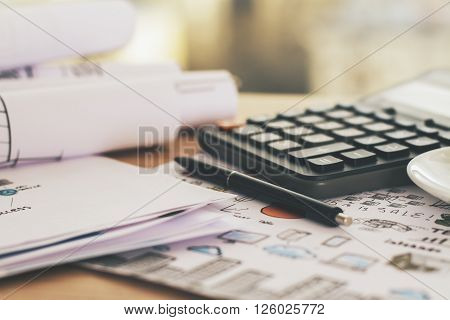 Sideview of wooden desktop with calculator and pen placed on business concept sketch