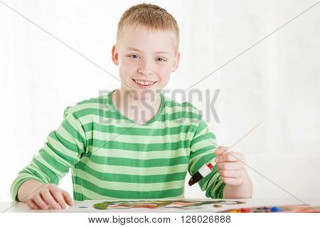 Seated Smiling Boy Holds Brush In Hand