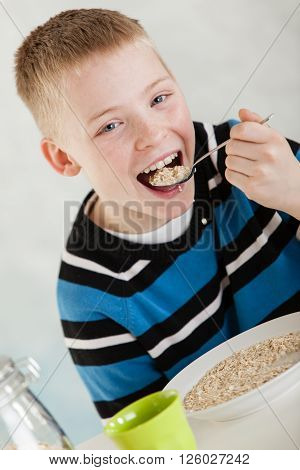 Single Child Putting Oatmeal In His Mouth