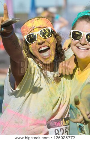 HAMPTON, GA - APRIL 2016: Female runners covered in colored corn starch celebrate finishing The Color Run in Hampton GA on April 2 2016 .