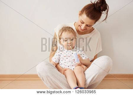 Portrait of young redhead mother having fun with her blond blue-eyed son playing indoor. Caring happy mother enjoying upbringing her lovely baby boy at the weekend at home. Pastel colors cozy scene
