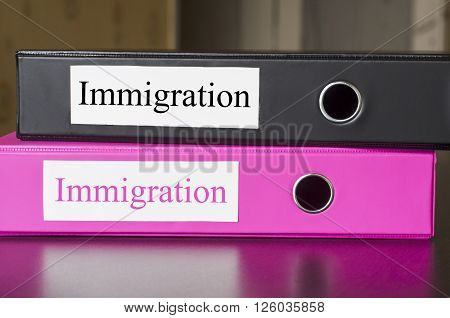 Bright office folders over dark background and immigrations text concept