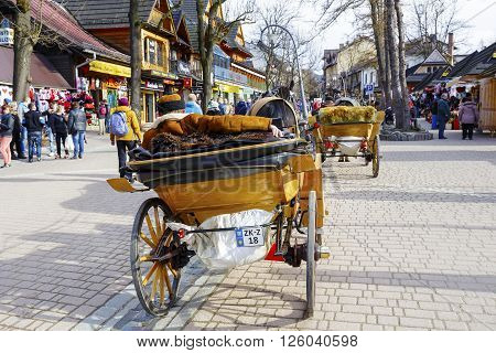 ZAKOPANE POLAND - MARCH 06 2016: Coachman with harnessed horse waits for customers at Krupowki street in main shopping area and pedestrian promenade in the city center of Zakopane