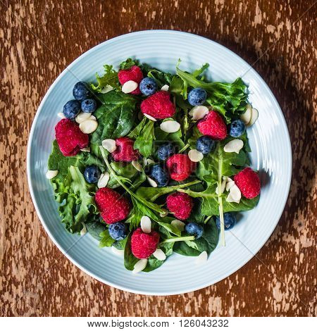 Green Salad With Berries And Almonds on rustic background