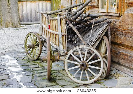 ZAKOPANE POLAND - MARCH 09 2016 Wooden waggon set against the wall of the building constructed in the traditional way with wooden logs. This scene reminds tradition of the region ** Note: Visible grain at 100%, best at smaller sizes