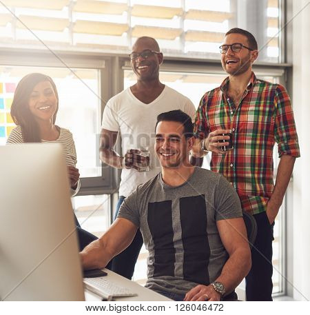 Happy Quartet Of Young Adults At Desk