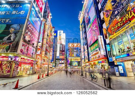 TOKYO, JAPAN - AUGUST 1, 2015: Crowds pass below colorful signs in Akihabara. The historic district electronics has evolved into the shopping area for video games, anime, manga, and computer goods.