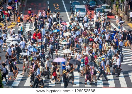TOKYO, JAPAN - JULY 29, 2015: Pedestrians at Shibuya crossing protect themselves from the summer heat with parasols. The crossing is considered one of the busiest in the world.
