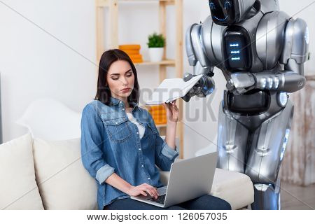 New generation. Gloomy serious beautiful girl sitting on the couch and using laptop while turning back from the book which robot is giving her