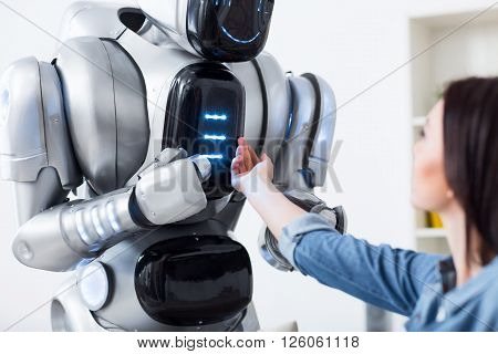 It is beating. Pleasant charming girl holding her hand on the robot and looking at it   while having a leisure time poster