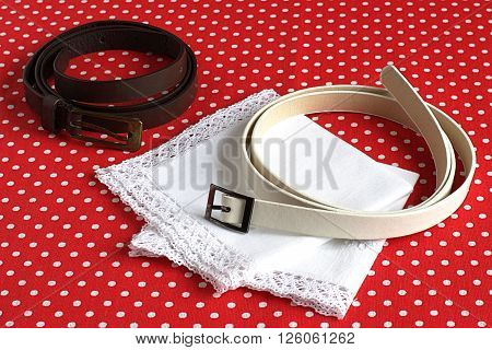 Two strap and two handkerchiefs on a red background with polka dots