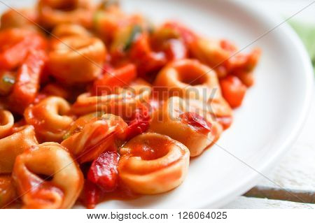 Tortellini Primavera Parmesan In Marinara Sauce On Wooden Rustic Background