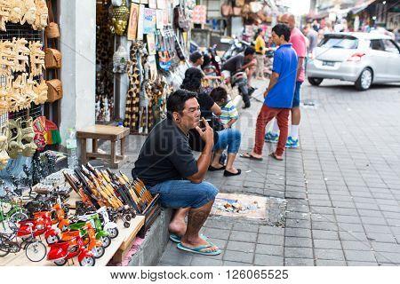 BALI, INDONESIA - FEB 24, 2016: Unidentified local street vendors, souvenir. During the peak tourist season in Legian - Kuta - Seminyak, the population increased to 200 thousand people.