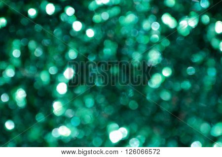 Bright and abstract blurred green rainbow background with shimmering glitter