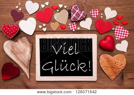 Chalkboard With German Text Viel Glueck Means Good Luck. Many Red Textile Hearts. Wooden Background With Vintage, Rustic Or Retro Style.