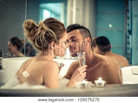 Young happy couple enjoying bath in the jacuzzi - Couple of lovers kissing in a jacuzzi pool