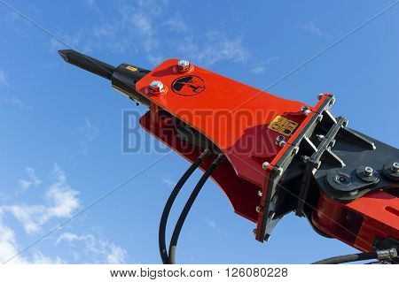 Hydraulic jackhammer for excavator, tractor, bulldozer and other construction machines, heavy industry, red demolition equipment, blue sky and white clouds on background