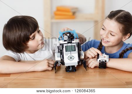 Have some fun . Cheerful pretty delighted   smiling children sitting at the table and  playing with robot while resting