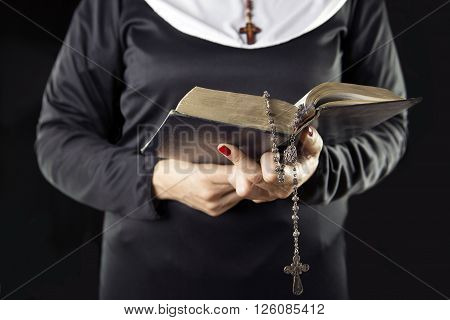 nun hands holding bible book over grey background