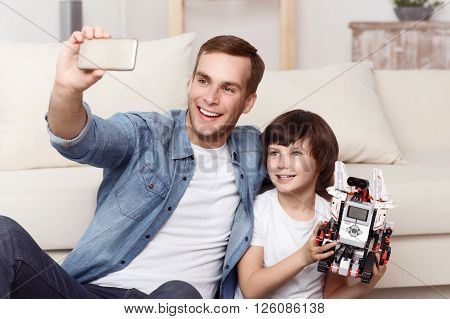 Crack a smile. Cheerful little son holding a robot and sitting on the floor with his father while making selfies