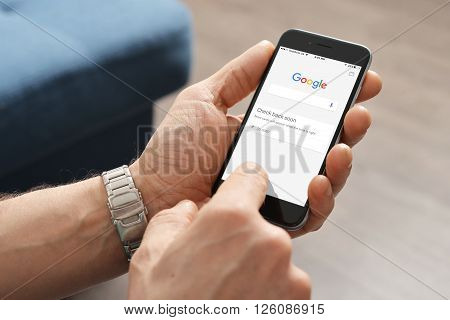 Kiev Ukraine - March 06 2016: A man touches on screen new Apple iPhone 6 smartphone device to open google application.