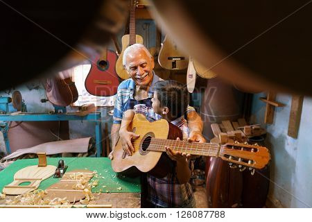 Small family business and traditions: old grandpa with grandson in lute maker shop. The senior artisan gives teaches how to play classic guitar to the boy who plays his first notes with the instrument