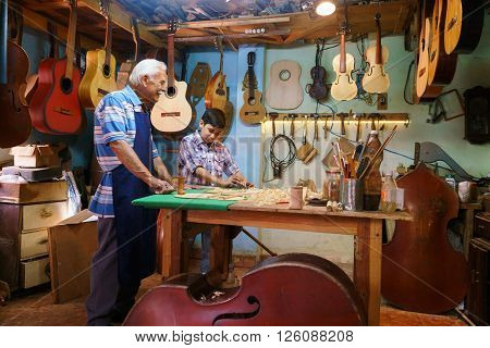 Small family business and traditions: old grandpa with grandson in lute maker shop. The senior artisan teaches to the boy how to chisel wood to make a music instrument