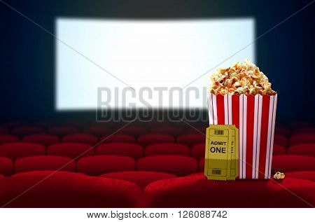 Cinema seat and pop corn facing empty movie screen
