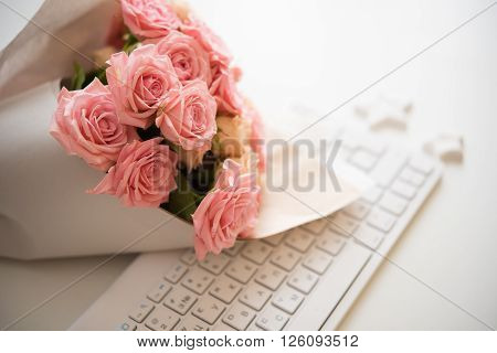 Bouquet of pink and beige roses on white computer keyboard, modern workplace closeup