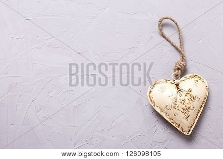 Beige decorative heart on grey textured background. Selective focus. Place for text.