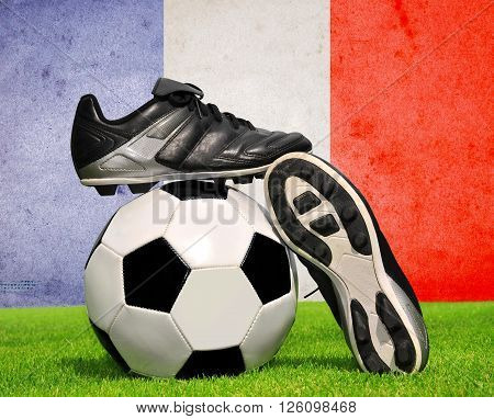 Soccer ball and cleats in grass in the background French flag