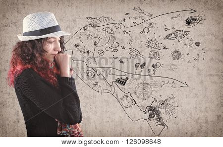 Young girl think about fantasy world drawing on wall.