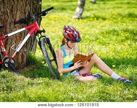 Bikes cycling girl wearing helmet read book on rest near bicycle. .