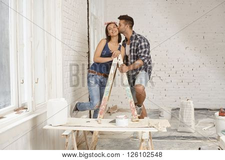 Kissing young couple standing on ladder at home renovation.