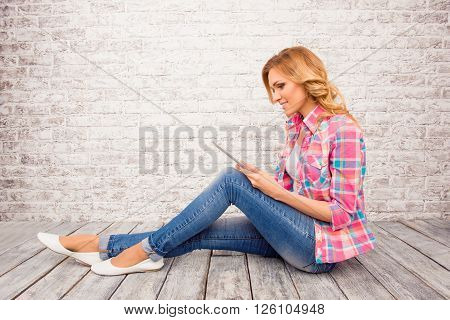 Side View Photo Of Young Girl Sitting On Floor With  Tablet