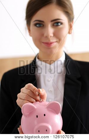 Hand Of Happy Smiling Businesswoman Putting Pin Money Into Pink Pig