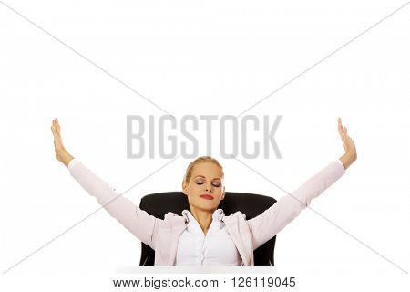 Beautiful business woman sitting behind the desk and stretching her arms