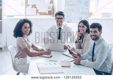 Best business team ever! Group of cheerful coworkers looking at camera with smile while sitting at the office table poster