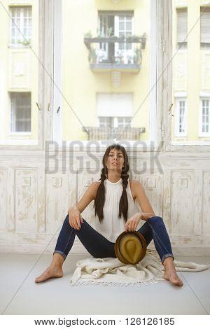 Pretty casual woman sitting on floor front of window, legs wide open.